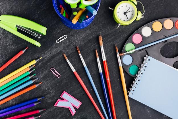 Artigos de papelaria multicoloridos desarrumado para criar arte em fundo escuro