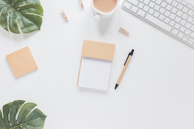 Artigos de papelaria na mesa branca com folhas verdes e teclado