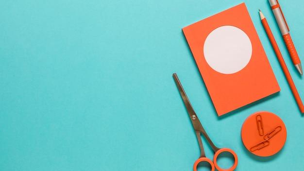Artigos de papelaria na superfície colorida