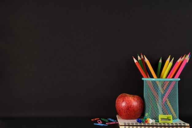 Artigos de papelaria ou material escolar com livros, lápis de cor, clipes e maçã vermelha em fundo preto.