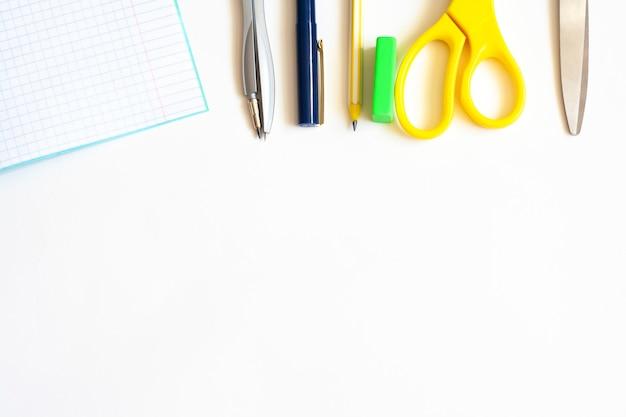 Artigos de papelaria para empresas em um fundo branco, caneta para caderno, lápis, bússola, borracha e tesoura, postura plana, espaço de cópia
