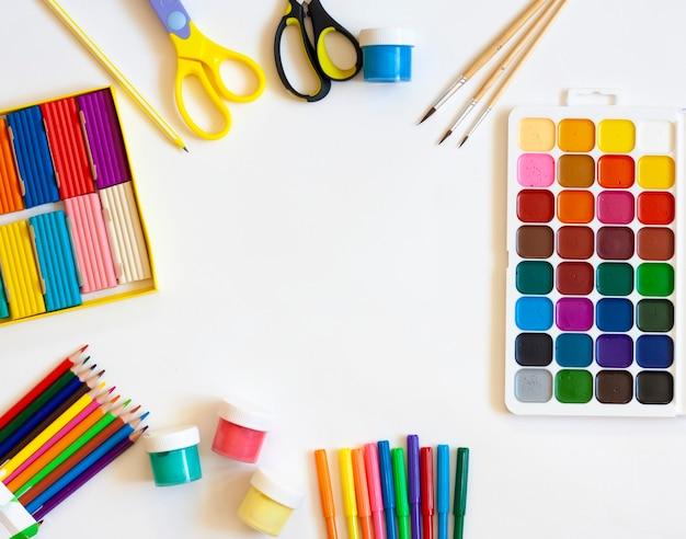 Artigos de papelaria para escola e trabalho criativo em fundo branco, tintas, lápis, marcadores, plasticina e tesoura, layed flat, copy space