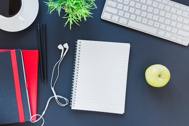 Artigos de papelaria perto da xícara de café e maçã na mesa com teclado