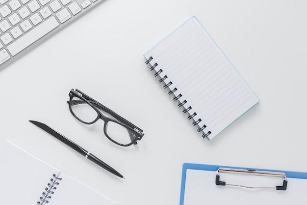 Artigos de papelaria perto de óculos e teclado na mesa branca