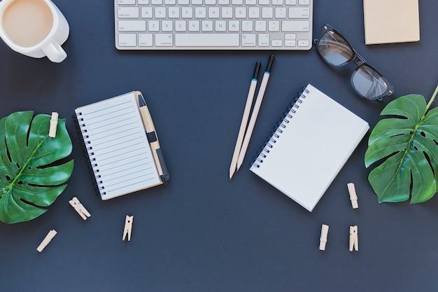Artigos de papelaria perto de teclado e xícara de café na mesa com folhas