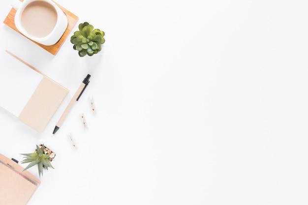 Artigos de papelaria perto de xícara de café e vasos de flores na mesa branca Foto Premium