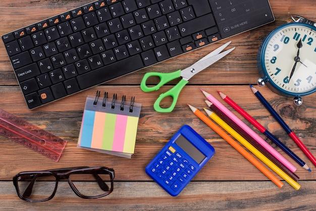 Artigos de papelaria planos leigos para lição de casa em um fundo de madeira. teclado de pc com régua, calculadora, tesoura e despertador em uma mesa marrom.