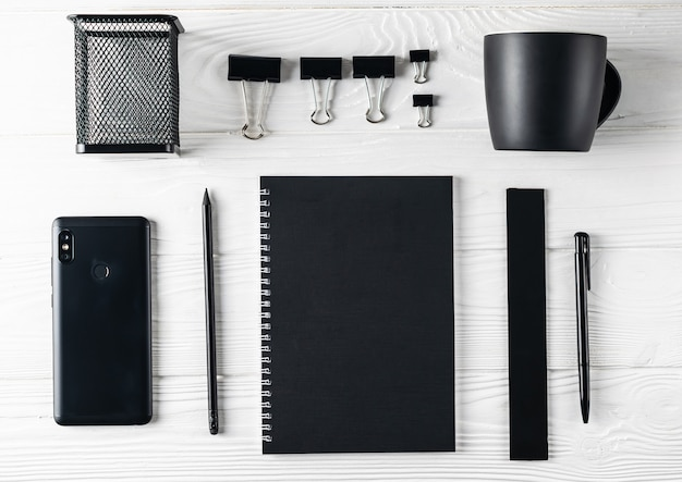 Artigos de papelaria pretos do negócio do escritório que incluem o café, caderno, pena, telefone