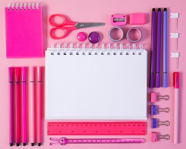 Artigos de papelaria rosa com um caderno