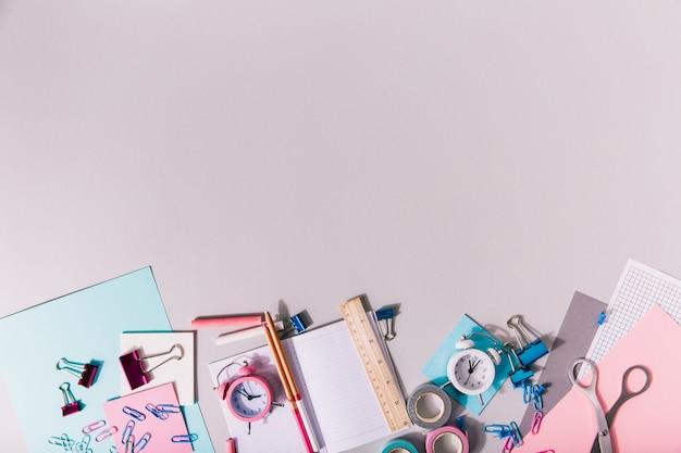 Artigos de papelaria rosa e azul retratados de forma criativa na parede