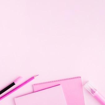 Artigos de papelaria rosa na superfície colorida
