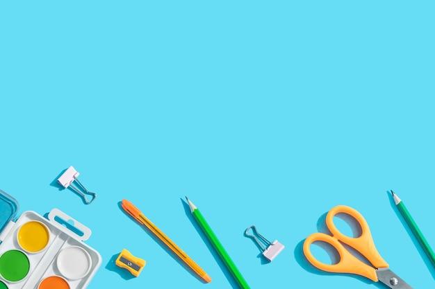 Artigos de papelaria: tesouras, canetas, lápis, clipes de papel, tintas aquarela. o conceito de aprendizagem, a criatividade das crianças. plano de fundo azul, vista superior, configuração plana, copie o espaço.