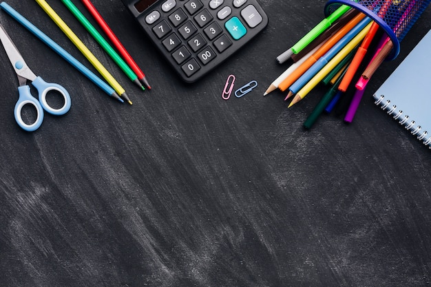 Artigos de papelaria vibrante e calculadora em fundo cinza