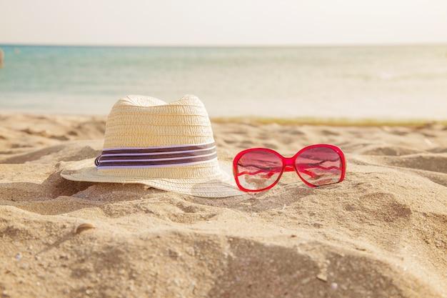 Artigos de praia na areia: óculos de sol, chapéu. viajar para o mar