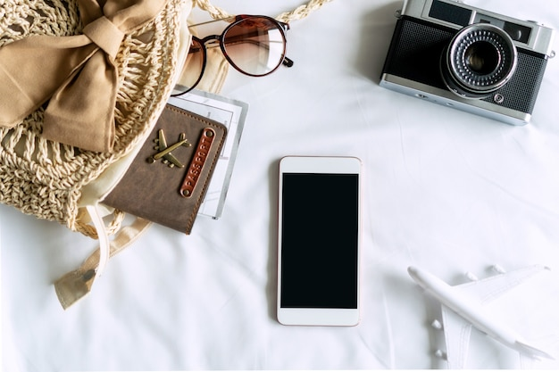 Artigos de viagem de uma mulher viajante com óculos de sol, bolsa, passaporte e celular no quarto em casa.
