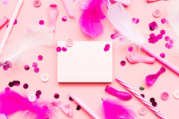 Artigos decorativos com o bloco de notas em branco no fundo rosa