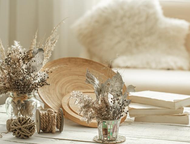 Artigos decorativos no interior aconchegante da sala, um vaso com flores secas na mesa de madeira clara.