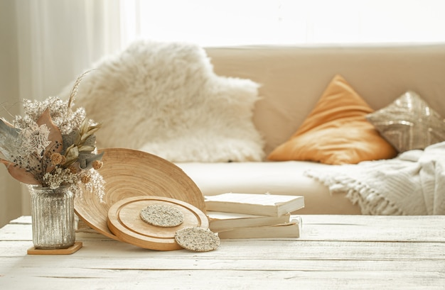 Artigos decorativos no interior aconchegante da sala, um vaso com flores secas sobre uma mesa de madeira clara.