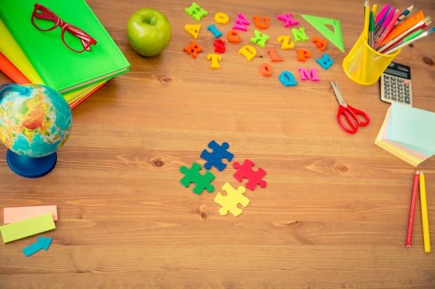 Artigos escolares na mesa de madeira em sala de aula. conceito de educação. vista do topo