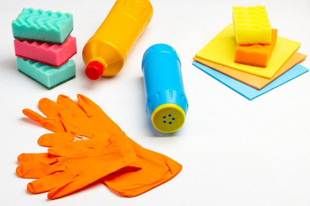 Artigos multicoloridos para limpar o apartamento. luvas de borracha laranja, frasco azul de pó, trapos e esponjas. fundo branco.