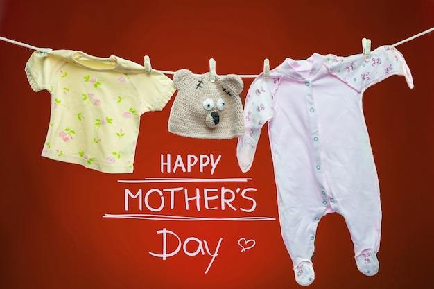 Artigos para bebês pendurados no varal sobre fundo vermelho. conceito de feliz dia das mães