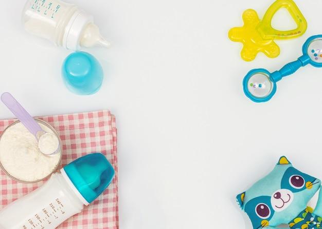 Artigos para bebês: talco para bebês, mamadeiras, mordedor, pufe, brinquedos para bebês na superfície branca