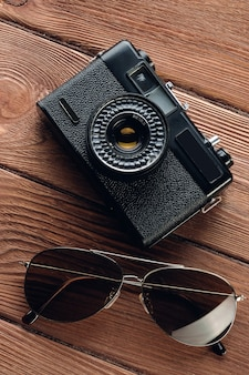 Artigos para férias de verão: câmera, óculos de sol. acessórios de viagem em um fundo de madeira. conjunto de layout turístico de um fotógrafo de rua.