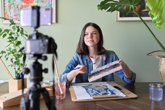 Artista, adolescente, desenha e grava em câmera de vídeo para seu blog. tintas, desenhos em uma mesa doméstica, câmera no tripé, desenho contando a garota blogueira vloger. tecnologia, arte, juventude, conceito de educação