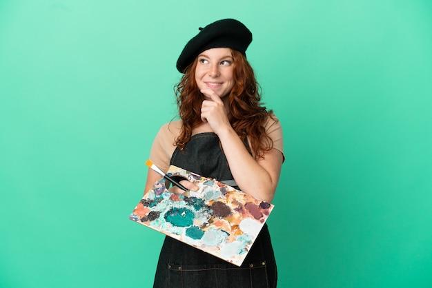 Artista adolescente ruiva segurando uma paleta isolada em um fundo verde e olhando para cima
