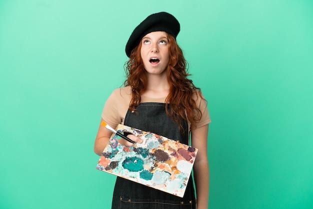 Artista adolescente ruiva segurando uma paleta isolada em um fundo verde olhando para cima e com expressão de surpresa