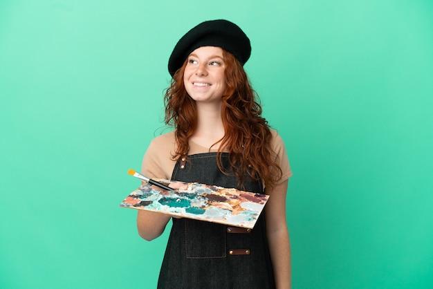 Artista adolescente ruiva segurando uma paleta isolada em um fundo verde pensando uma ideia enquanto olha para cima
