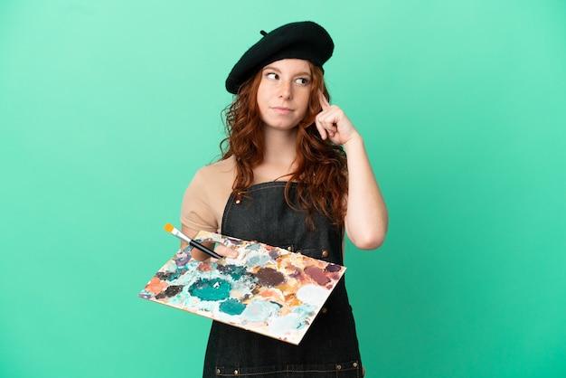 Artista adolescente ruiva segurando uma paleta isolada em um fundo verde, tendo dúvidas e pensando