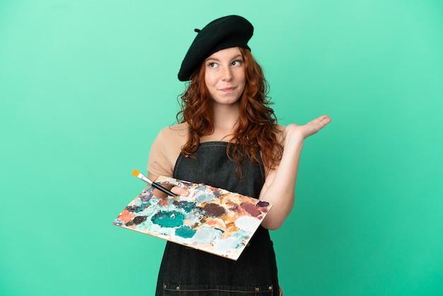 Artista adolescente ruiva segurando uma paleta isolada em um fundo verde, tendo dúvidas enquanto levanta as mãos