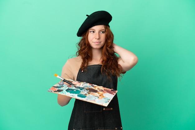 Artista adolescente ruiva segurando uma paleta isolada em um fundo verde, tendo dúvidas