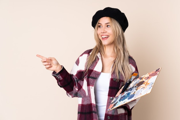 Artista adolescente segurando uma paleta isolada em azul apontando o dedo para o lado e apresentando um produto
