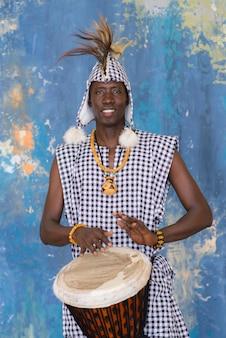 Artista africana em roupas tradicionais tocando djembe drum