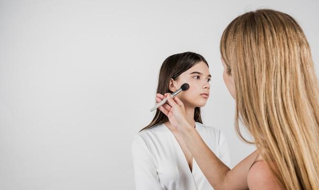 Artista aplicando blush no modelo bonito