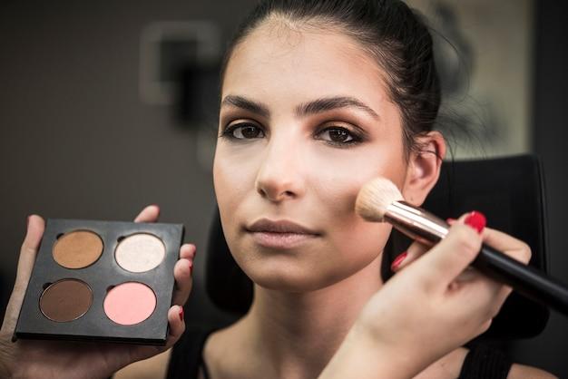 Artista aplicando blush no modelo