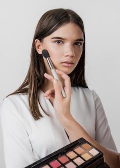 Artista aplicando maquiagem no modelo