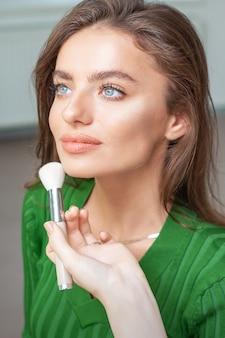 Artista aplicando maquiagem profissional de base tonal no rosto de uma bela jovem caucasiana na sala de maquiagem. base para maquiagem.