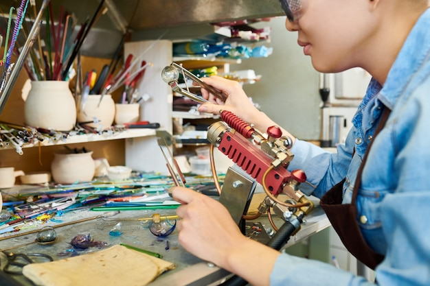 Artista asiático fazendo lampwork no estúdio