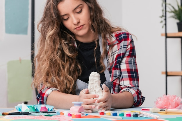 Artista atraente fazendo artesanato arte usando argila branca