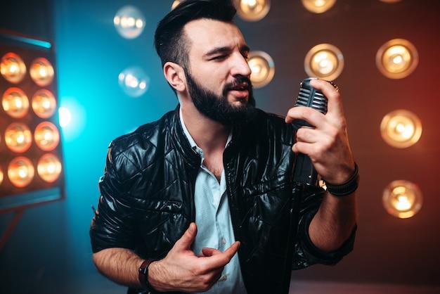 Artista barbudo com microfone canta uma música