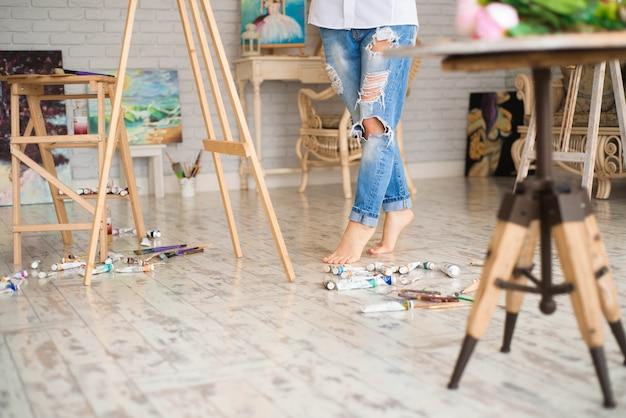 Artista bonito bonito da menina que pinta uma imagem em uma lona em uma armação. fundo branco do estúdio. cabelos longos, morena. segurando o pincel colorido e paleta.