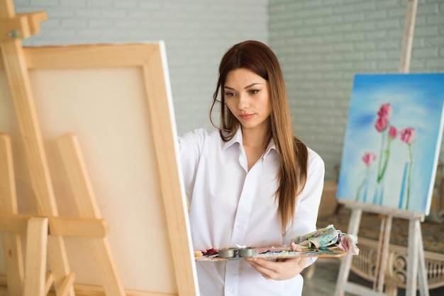 Artista bonito bonito da menina que pinta uma imagem em uma lona em uma armação.