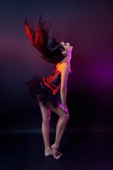 Artista burlesco com espartilho preto e vermelho, foto de estúdio