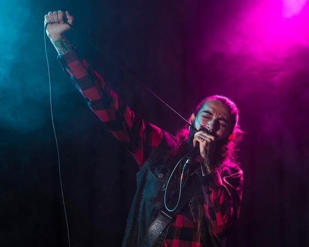 Artista cantando e segurando o cabo do microfone