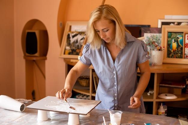 Artista cobre a superfície da tela com tinta branca usando espátula para inspiração e criatividade. pintura de interiores. design moderno.