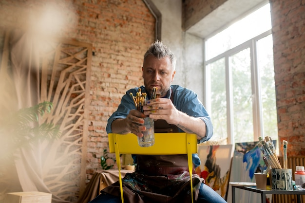 Artista contemporâneo de meia-idade sentado em uma cadeira amarela em um estúdio e escolhendo o pincel de um ramo de vidro