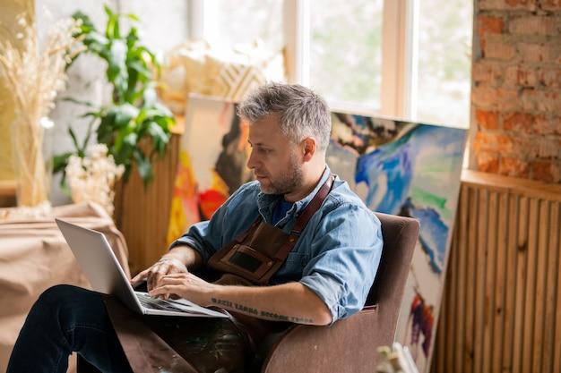 Artista contemporâneo sério com laptop sentado em uma poltrona em um estúdio enquanto navega na internet em busca de ideias criativas